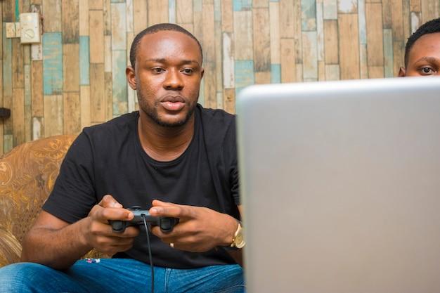 Jonge knappe afrikaanse man die serieus spel speelt op zijn laptop