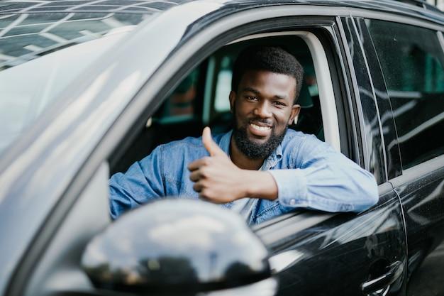 Jonge knappe afrikaanse man duimen opdagen terwijl hij zijn auto bestuurt