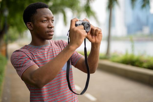 Jonge knappe afrikaanse man fotograferen met camera in park