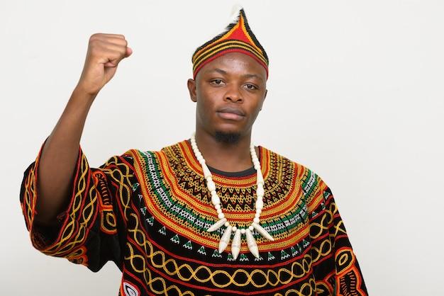 Jonge knappe afrikaanse man in traditionele kleding met opgeheven vuist