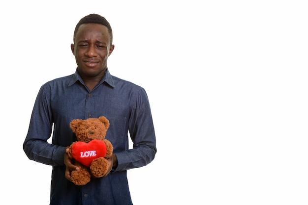 Jonge knappe afrikaanse man kijkt verdrietig terwijl hij teddybeer vasthoudt