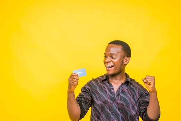 Jonge knappe afrikaanse man klaar om online te winkelen met zijn creditcard crediteur betaalkaart