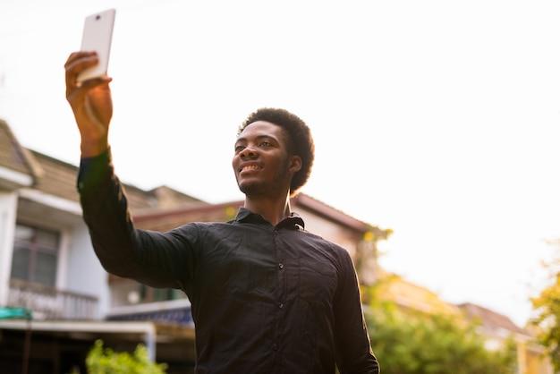 Jonge knappe afrikaanse man met behulp van mobiele telefoon buitenshuis