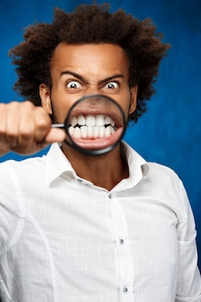 Jonge knappe afrikaanse man poseren met vergrootglas over blauwe muur.