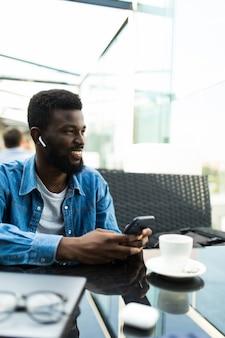 Jonge knappe afrikaanse man praten aan de telefoon via oor bonen zittend in café