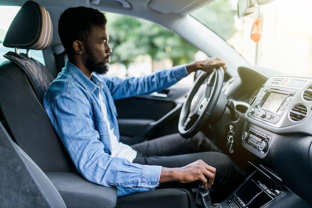 Jonge knappe afrikaanse man schakelen tijdens het autorijden