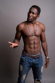 Jonge knappe afrikaanse man shirtless tegen een grijze achtergrond