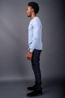 Jonge knappe afrikaanse man tegen een grijze achtergrond