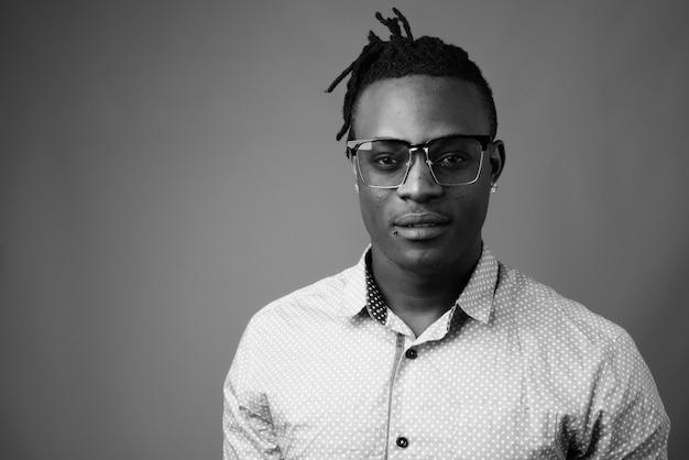Jonge knappe afrikaanse man uit kenia tegen grijze muur in zwart en wit