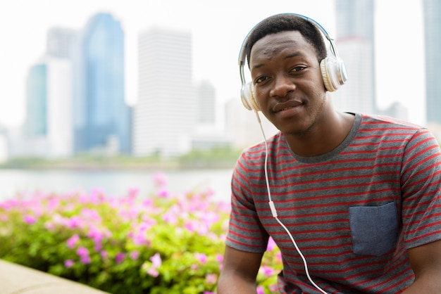 Jonge knappe afrikaanse man zit in het park tijdens het luisteren naar muziek met een koptelefoon