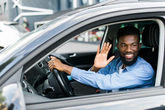Jonge knappe afrikaanse man zwaait de groeten naar iemand terwijl hij zijn auto bestuurt