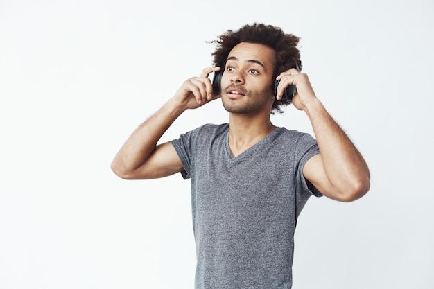 Jonge knappe afrikaanse mens die aan muziek in hoofdtelefoons luistert