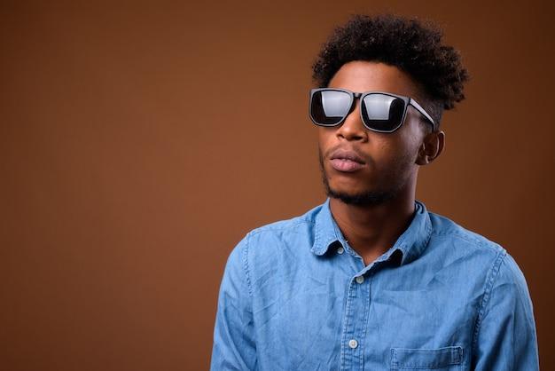 Jonge knappe afrikaanse mens die op bruin denkt