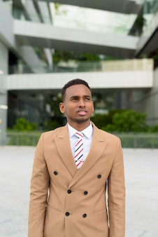 Jonge knappe afrikaanse zakenman denken in de stad buitenshuis