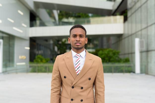 Jonge knappe afrikaanse zakenman draagt pak in de stad buitenshuis