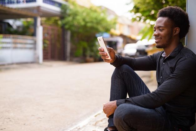 Jonge knappe afrikaanse zakenman in de straten buiten