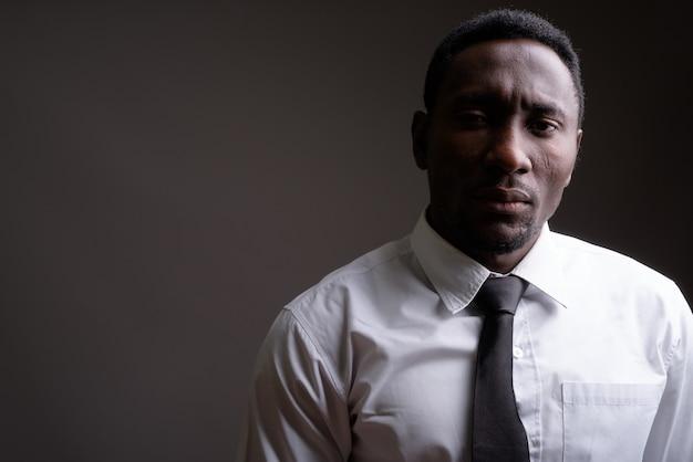 Jonge knappe afrikaanse zakenman tegen grijze achtergrond