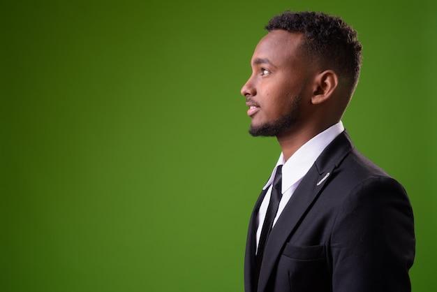 Jonge knappe afrikaanse zakenman tegen groene achtergrond