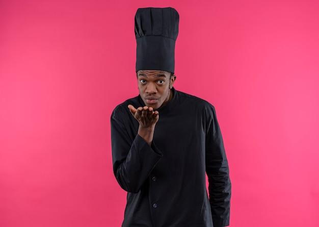 Jonge knappe afro-amerikaanse kok in uniform chef-kok stuurt kus geïsoleerd op roze muur