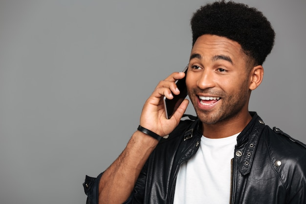 Jonge knappe afro-amerikaanse man praten op mobiele telefoon, opzij kijken