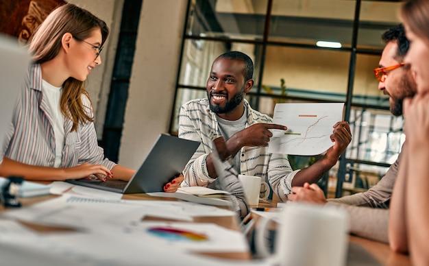 Jonge knappe afro-amerikaanse zakenman die een grafiek op papier toont aan een groep collega's die aan een tafel zitten met laptops in een modern kantoor.