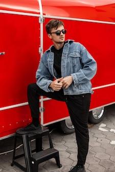 Jonge knappe amerikaanse hipster man in stijlvolle zwarte broek in een t-shirt in een blauwe trendy denim jasje poseren in de buurt van een rode vintage auto in de stad. aantrekkelijke moderne kerel. straat jeugdmode. herenkleding.