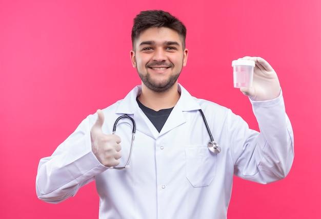 Jonge knappe arts die witte medische toga draagt, witte medische handschoenen en een stethoscoop blij met resultaten in transparante analysecontainer die zich over roze muur bevindt