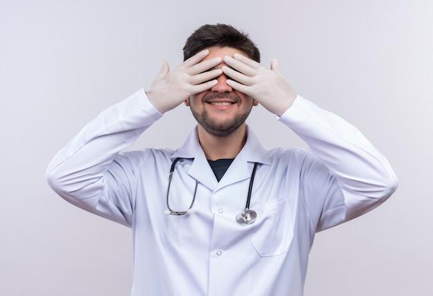 Jonge knappe arts die witte medische toga draagt, witte medische handschoenen en stethoscoop die huid en ziek speelt die zich gelukkig over witte muur bevindt