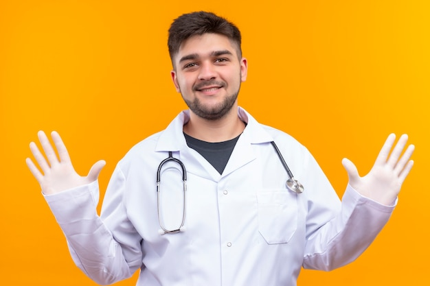 Jonge knappe arts die witte medische toga draagt, witte medische handschoenen en stethoscoop die openende wapens glimlacht en hallo zegt die zich over oranje muur bevindt