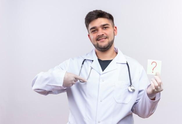 Jonge knappe arts die witte medische toga draagt, witte medische handschoenen en stethoscoop glimlachend wijzend op het vraagteken ter beschikking die zich over witte muur bevinden