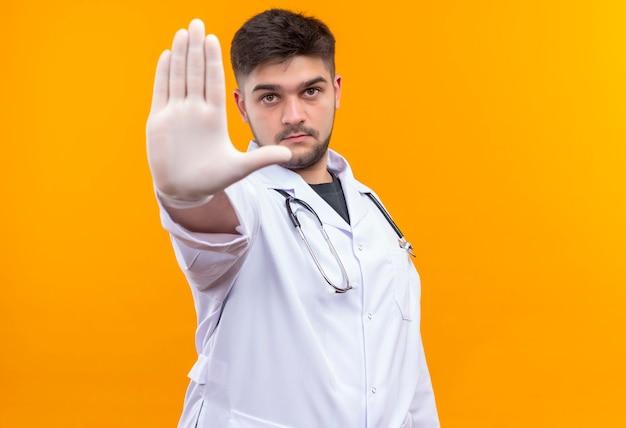 Jonge knappe arts die witte medische toga draagt, witte medische handschoenen en stethoscoop kijkt die ernstig stopbord met rechterhand toont die zich over oranje muur bevindt