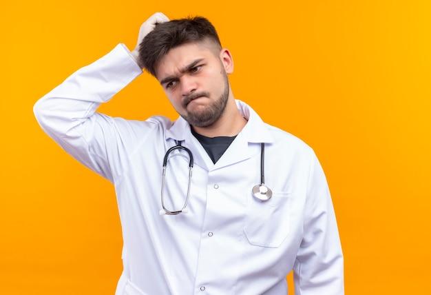 Jonge knappe arts die witte medische toga draagt, witte medische handschoenen en stethoscoop kijkt die verward zijn hoofd krabt met hand die zich over oranje muur bevindt
