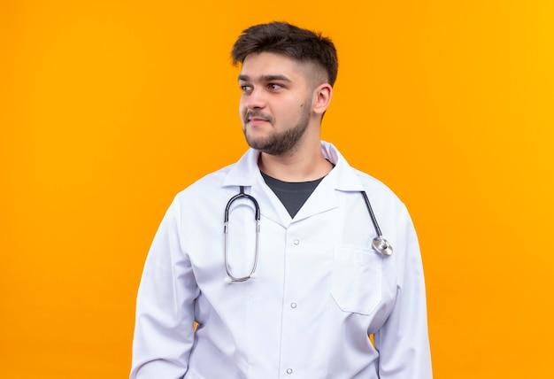 Jonge knappe arts die witte medische toga, witte medische handschoenen en een stethoscoop draagt die naast zich over oranje muur ook glimlachend glimlachen