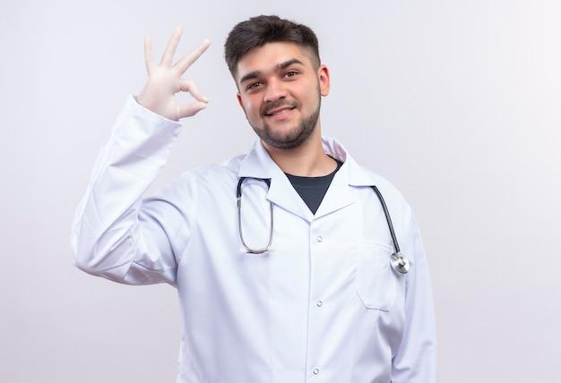Jonge knappe arts die witte medische toga witte medische handschoenen en stethoscoop draagt die gelukkig ok teken met wapen tonen die zich over witte muur bevinden
