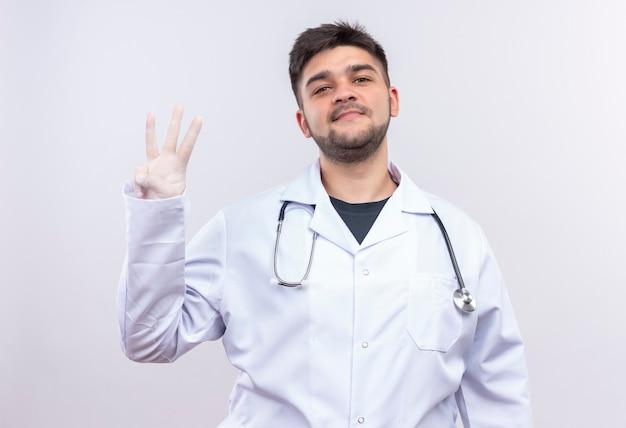 Jonge knappe arts die witte medische toga, witte medische handschoenen en stethoscoop draagt die graag drie teken met vingers toont die zich over witte muur bevinden