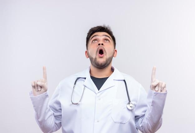 Jonge knappe arts die witte medische toga, witte medische handschoenen en stethoscoop draagt die met wijsvingers omhoog wijst die zich over witte muur bevinden