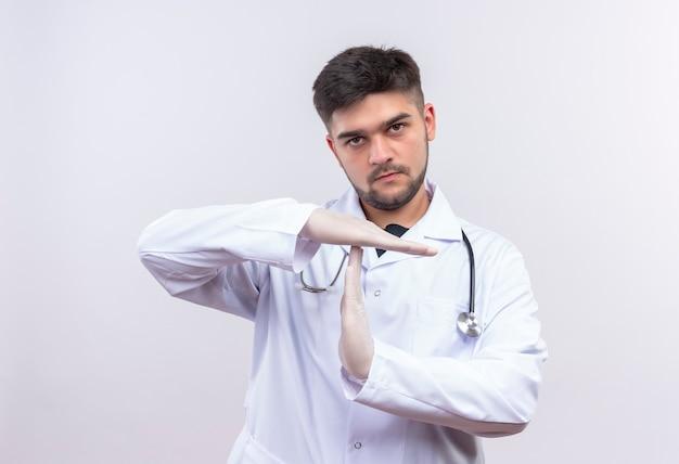 Jonge knappe arts die witte medische toga witte medische handschoenen en stethoscoop draagt die pauze met handen tonen die zich over witte muur bevinden