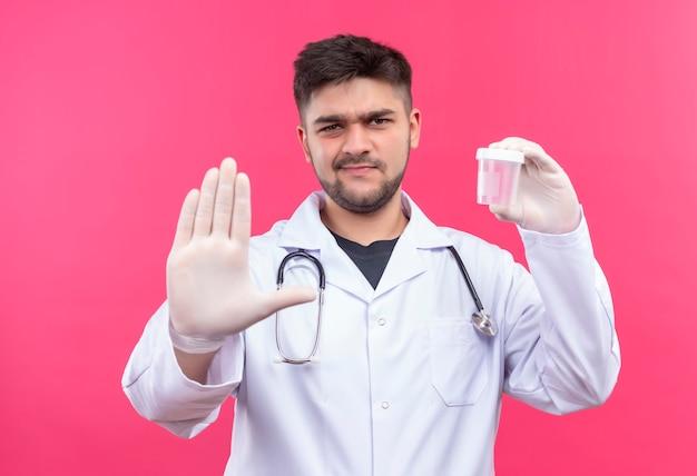 Jonge knappe arts die witte medische toga, witte medische handschoenen en stethoscoop draagt, die transparante analysecontainer houdt die stopbord met hand doet die zich over roze muur bevindt