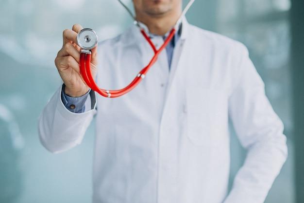 Jonge knappe arts in een medische robe met stethoscoop