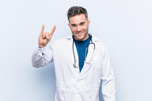 Jonge knappe artsenmens die een hoornengebaar toont als revolutie.