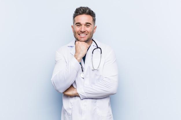 Jonge knappe artsenmens die gelukkige en zekere, uching kin met hand glimlachen.