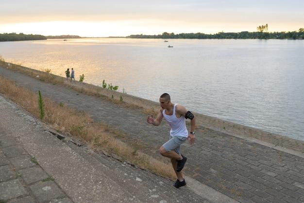 Jonge knappe atleet die boven door de rivierbank loopt