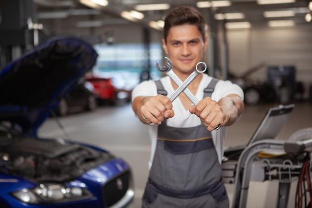 Jonge knappe autowerktuigkundige die voertuig in zijn garage herstelt