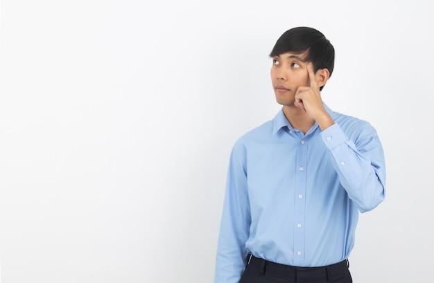 Jonge knappe aziatische bedrijfsmens die een idee denken terwijl geïsoleerd kijken omhoog