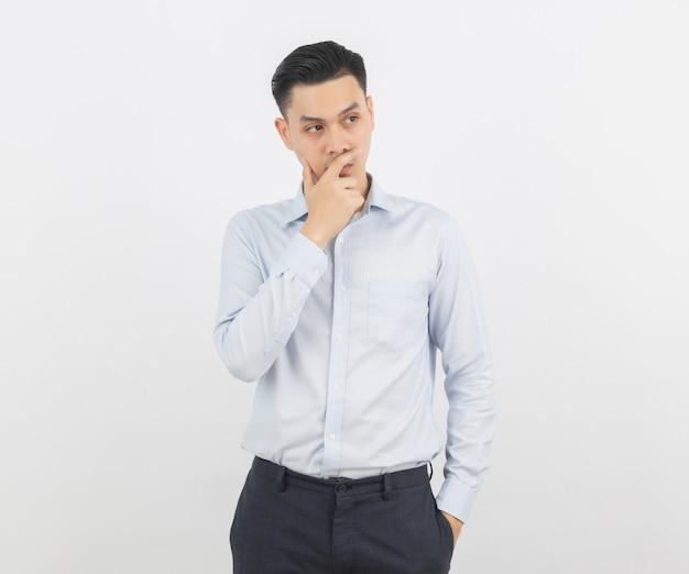 Jonge knappe aziatische bedrijfsmens die een idee denken terwijl omhoog het kijken