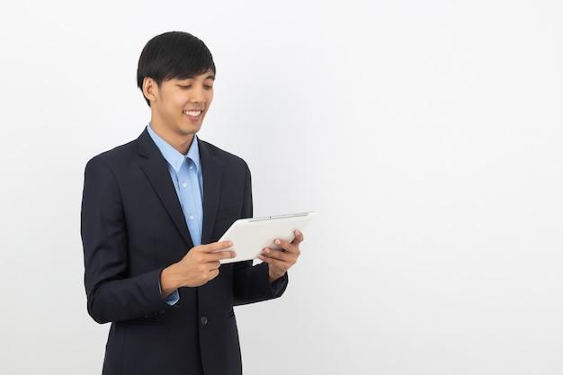 Jonge knappe aziatische bedrijfsmens die en aan tabletcomputer spelen kijken met het glimlachen