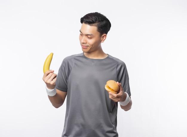 Jonge knappe aziatische de holdingsbanaan en hamburger van de sportmens