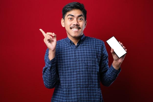 Jonge knappe aziatische man die het scherm van een smartphone over een rode geïsoleerde achtergrond laat zien, erg blij met de hand en de vinger naar de zijkant te wijzen