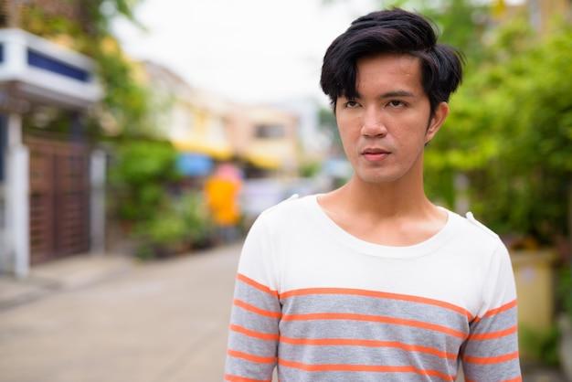 Jonge knappe aziatische man in de straten buiten