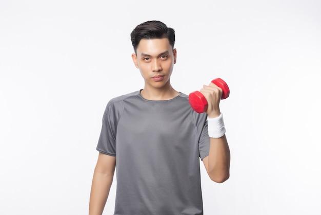 Jonge knappe aziatische man in sport outfits oefenen met halters